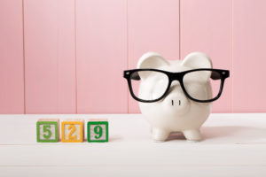 529 college savings plan theme with white piggy bank with Eyeglasses on pink wooden wall
